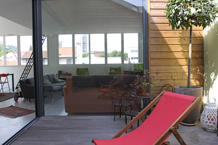 Deck chairs, plants, wood paneling. C0587