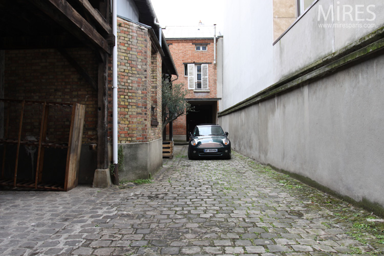 Cobblestone courtyard and wooden shed. C0607