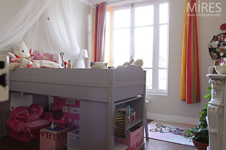 Gray loft bed and multicoloured curtains. C0646