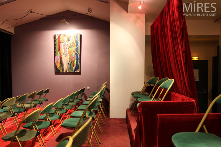 Small hall and stage, red curtains, green chairs. C0685