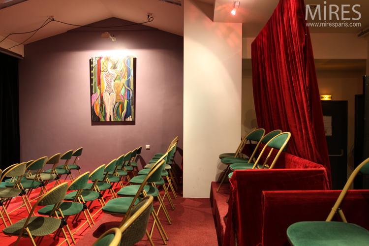 Petite salle avec une scène, rideaux rouges, chaises vertes. C0685