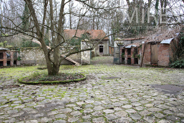 Paved courtyard and brick hutches. C0985