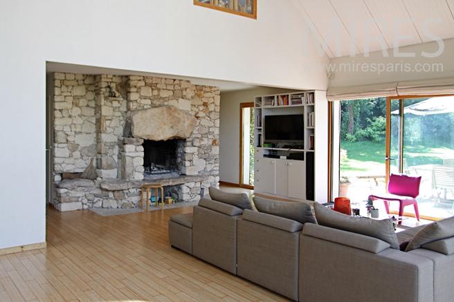 Salon lumineux avec sa cheminée en pierre. C1233