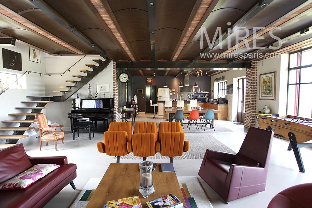 Très large salon carré avec piano. C1463