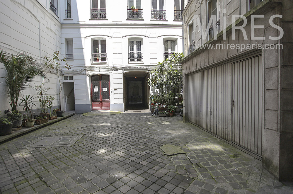Paved courtyard with garage. C0101