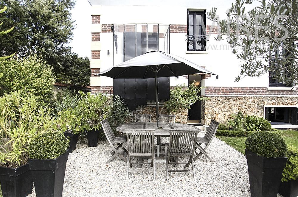 Terrasse sur gravier avec plantes vertes. C1595