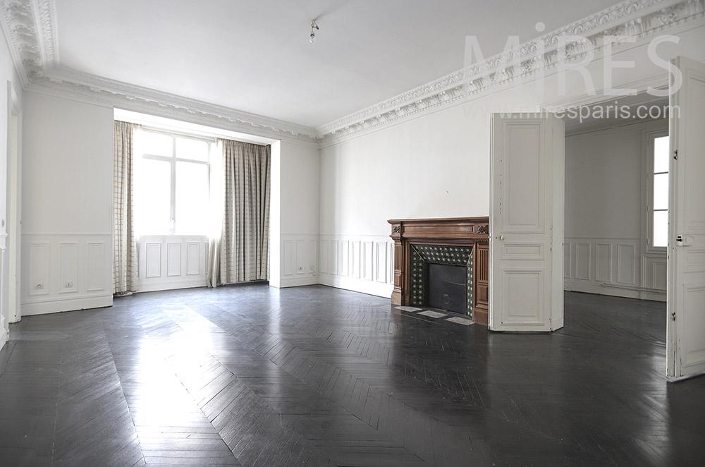 Cheminée brune, sol noir, mur blanc. C1654