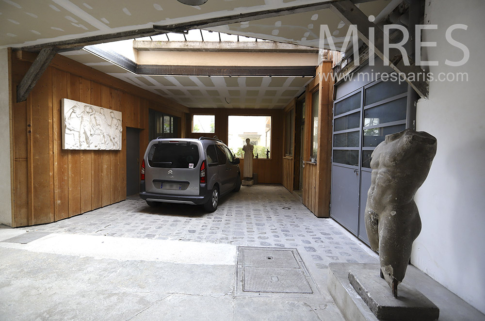 Garage, wooden wall and sculptures. C1875